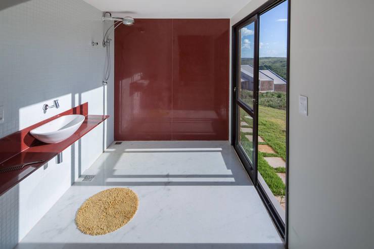 Casa Popsonics - Lab 606 Arquitetos: Banheiros  por Joana França