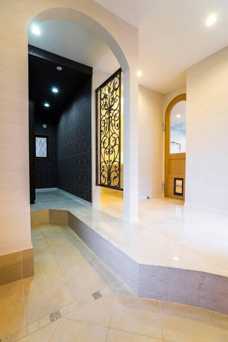 アーチとアイアンが印象的な遊び心ある南欧風の住まい: QUALIAが手掛けた廊下 & 玄関です。