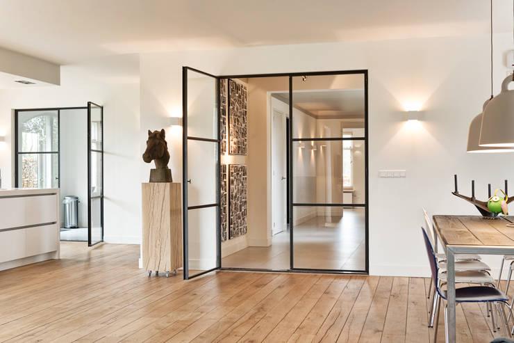Deze stoere industriële stalen deuren geven een bijzondere uitstraling aan de woning:  Woonkamer door Jolanda Knook interieurvormgeving