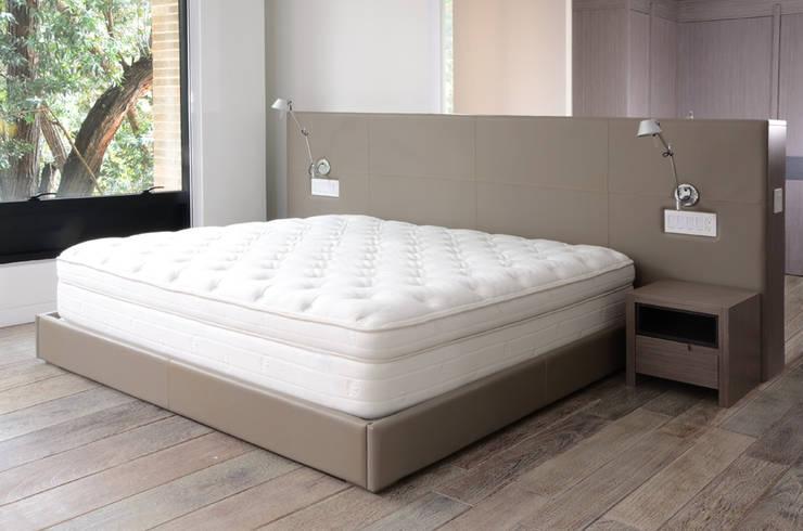 Espaldar en cuero. : Dormitorios de estilo  por Justiniano Alfonso,
