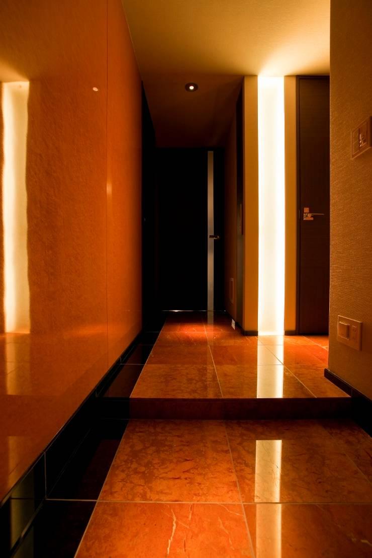 光の演出が冴える非日常空間でタワーライフを楽しむ: QUALIAが手掛けた廊下 & 玄関です。