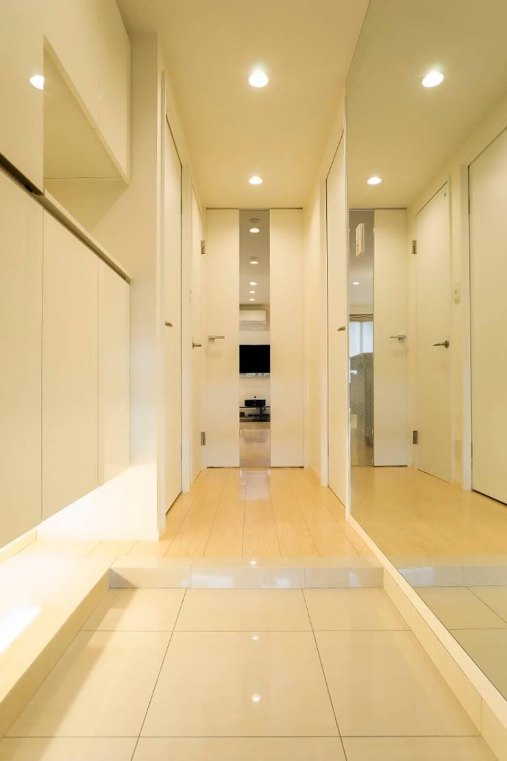 ベネツィアンモザイクタイルが映えるホワイトを基調とした上品な空間: QUALIAが手掛けた廊下 & 玄関です。