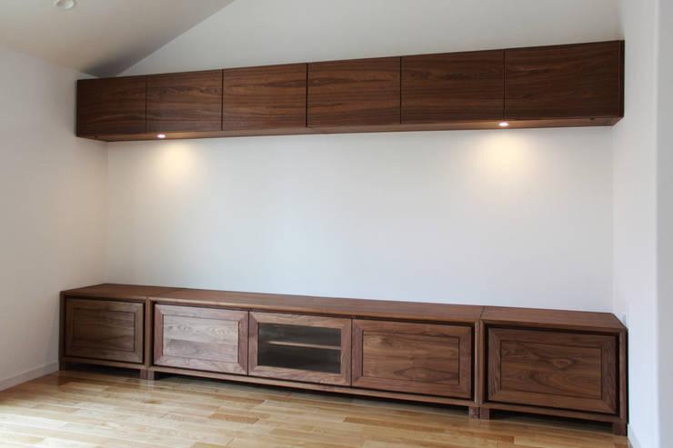ウォールナット材のオーダー壁面収納: Vigore interior&galleryが手掛けたリビングルームです。