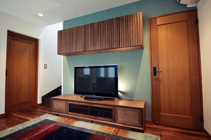 陰影を生かしたデザインの壁面テレビボード: Vigore interior&galleryが手掛けたリビングルームです。
