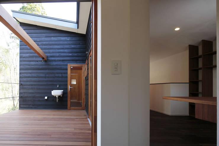 森を眺める黒い家: 一級建築士事務所あとりえが手掛けたテラス・ベランダです。
