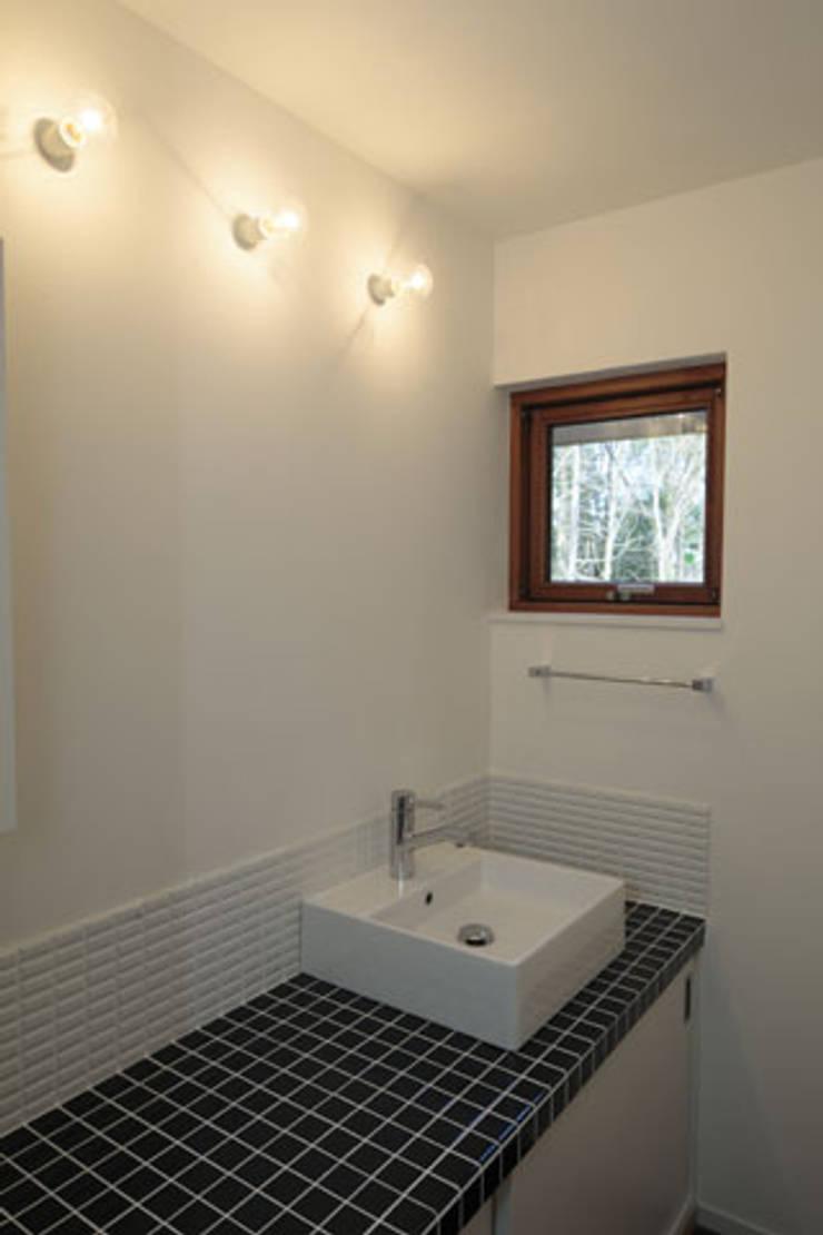 森を眺める黒い家: 一級建築士事務所あとりえが手掛けた浴室です。