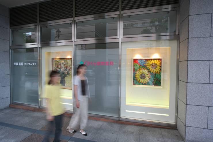 薬局 外観部分(通りに向けた画廊風ディスプレイ 絵画 昼): 吉田設計+アトリエアジュールが手掛けた医療機関です。