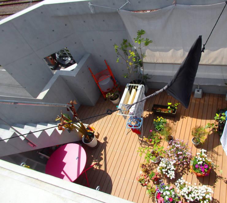 多彩なコンクリート壁の家: ユミラ建築設計室が手掛けたベランダです。