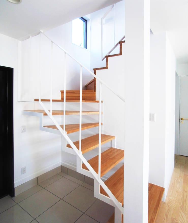 庭を囲む家: ユミラ建築設計室が手掛けた廊下 & 玄関です。,