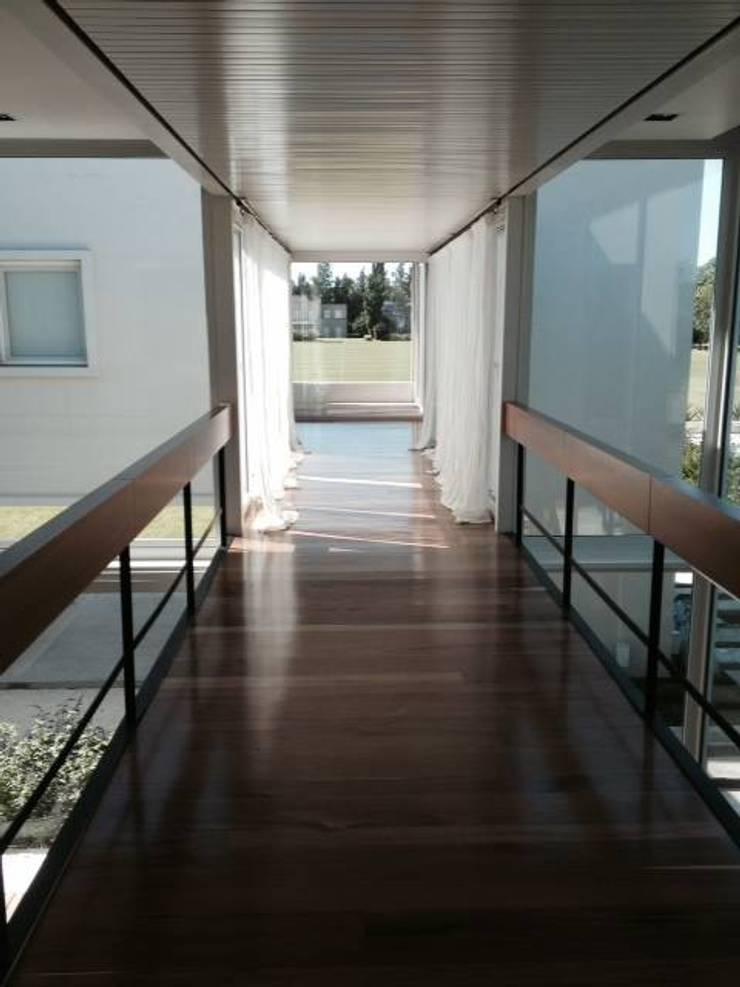 Casa Moderna: Pasillos y recibidores de estilo  por GG&A,