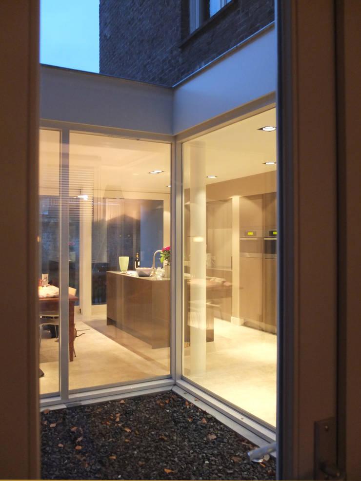 Kleine patio tussen woonkamer en -keuken :  Huizen door Engelman Architecten BV