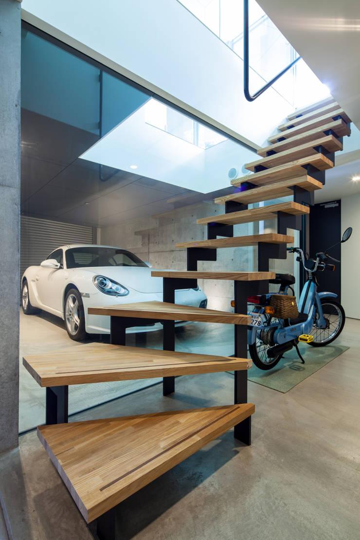 玄関ホールから眺める事ガレージ: 田中一郎建築事務所が手掛けた廊下 & 玄関です。,