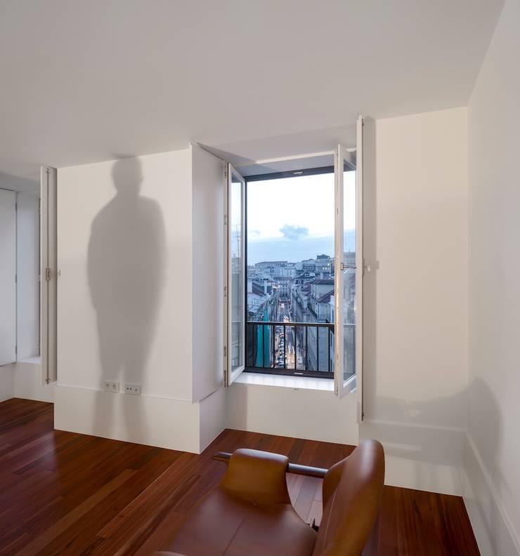 Edifício Chinesas Milagrosas - Vista da sala para janela: Salas de estar  por Posto9 Arquitectos