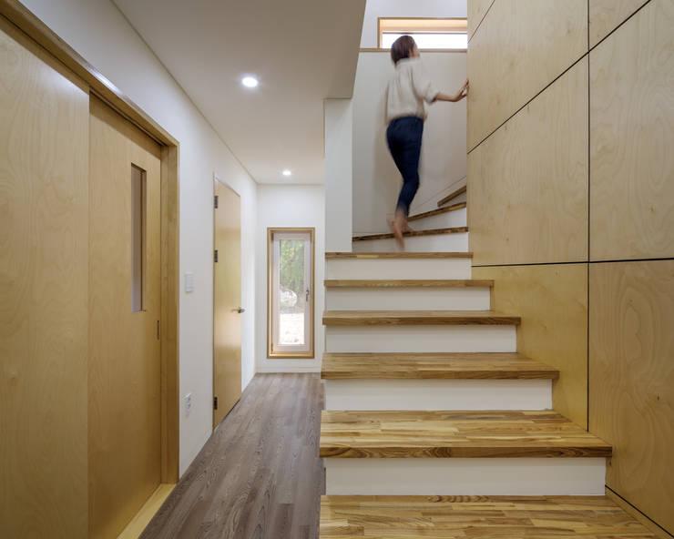 Pasillos y hall de entrada de estilo  por B.U.S Architecture