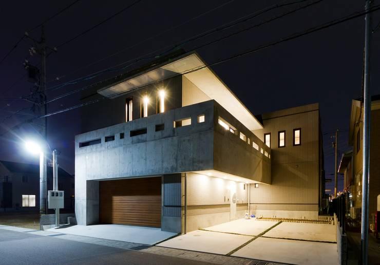 中庭に暖炉がある、曲面のファサードと、打ち放しのスクエアなファサードの二世帯住宅: イデア建築デザイン事務所が手掛けた家です。