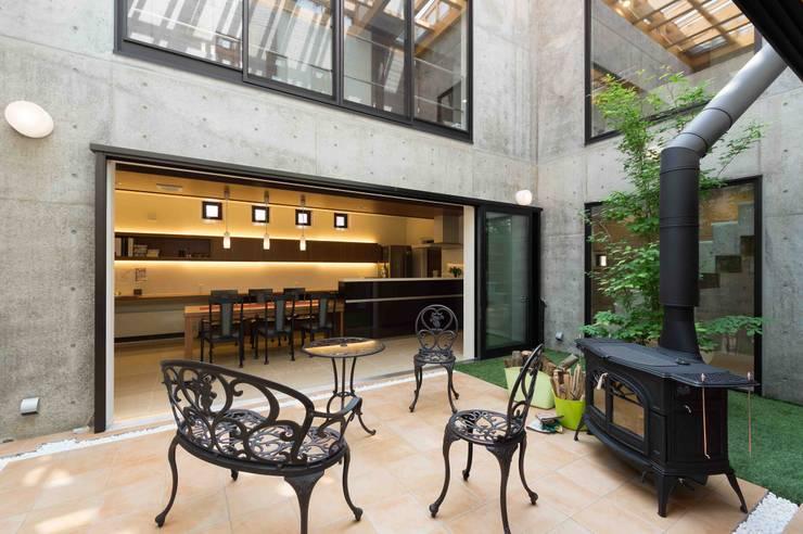 中庭から見るダイニングキッチン: イデア建築デザイン事務所が手掛けたテラス・ベランダです。
