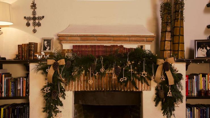Chimenea en el proceso de adornarla para Navidad. de MARIANGEL COGHLAN