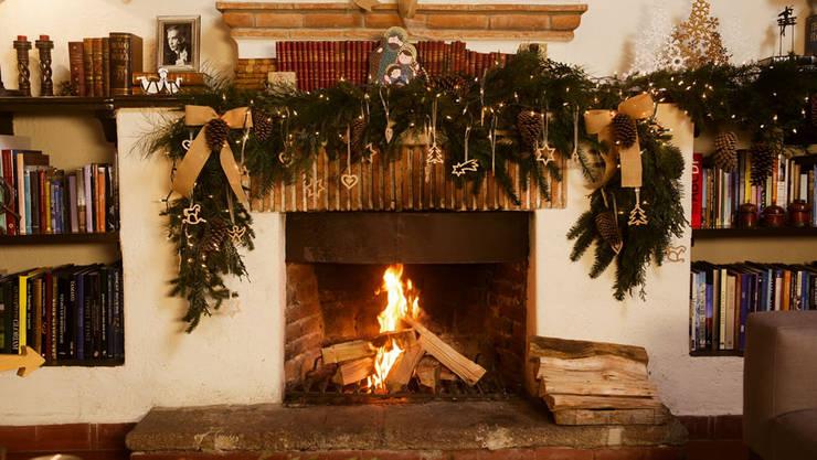 Chimenea encendida y adornada para Navidad.:  de estilo  por MARIANGEL COGHLAN