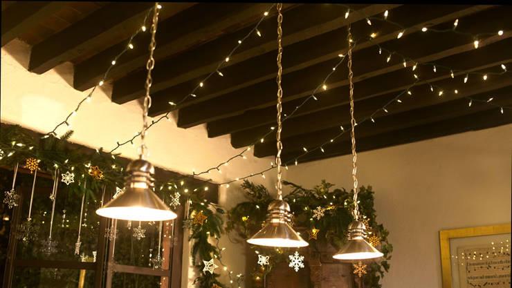 Colocando las luces navideñas en el techo.:  de estilo  por MARIANGEL COGHLAN