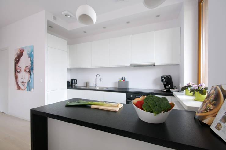Biała kuchnia z laminowanym czarnym blatem: styl , w kategorii Kuchnia zaprojektowany przez ZAWICKA-ID Projektowanie wnętrz