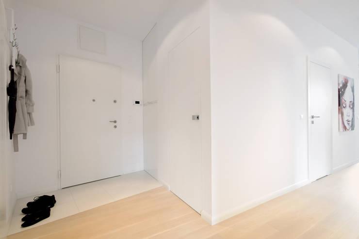Minimalistyczny przedpokój z drzwiami zlicowanymi ze ścianą: styl , w kategorii Korytarz, przedpokój zaprojektowany przez ZAWICKA-ID Projektowanie wnętrz