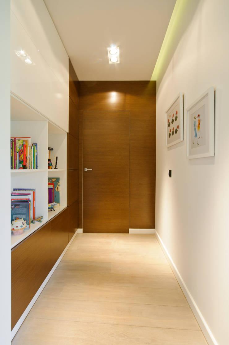 Korytarz z biblioteczką i zlicowanymi drzwiami ze ścianą: styl , w kategorii Korytarz, przedpokój zaprojektowany przez ZAWICKA-ID Projektowanie wnętrz,Nowoczesny