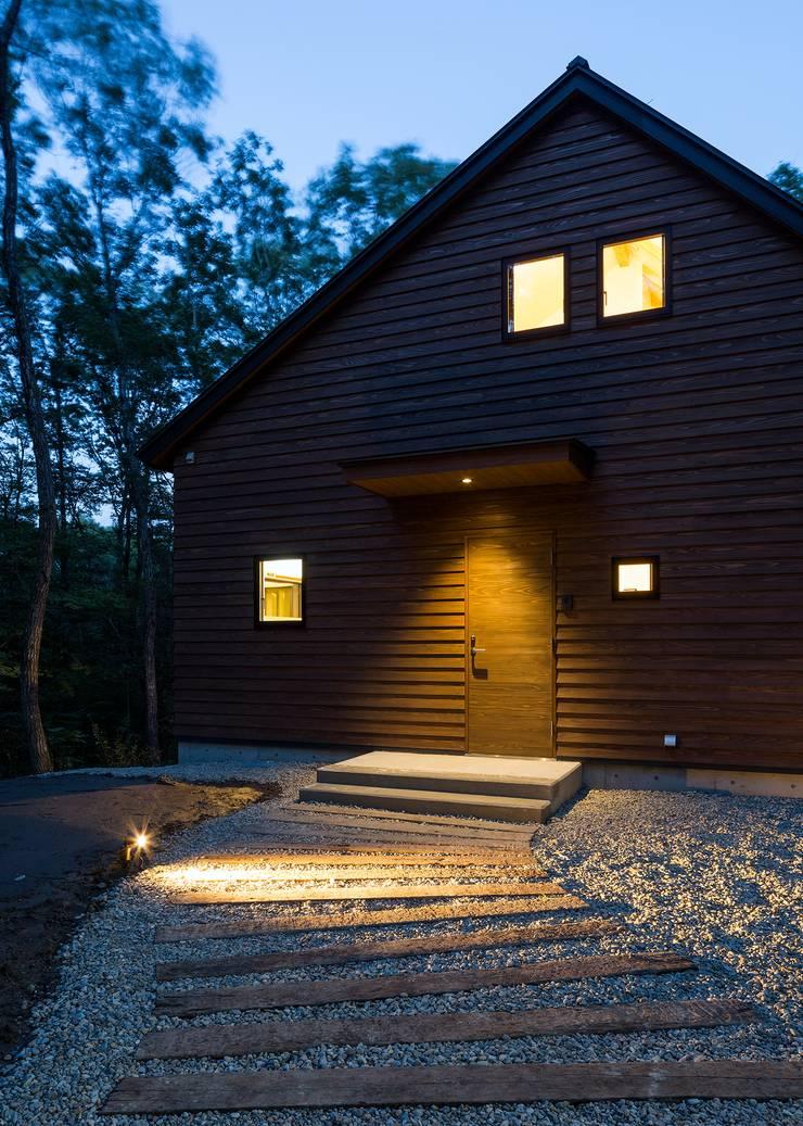 アプローチ(夜景): Unico design一級建築士事務所が手掛けた家です。,