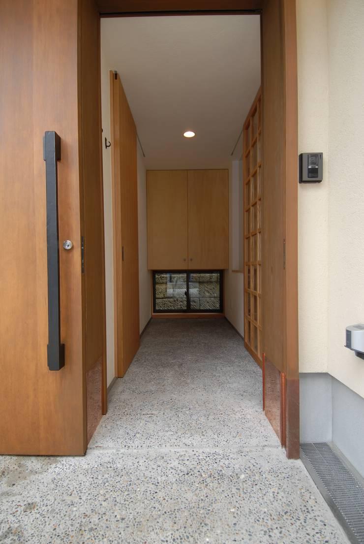 洗い出し土間のあるエントランス空間: 株式会社TERRAデザインが手掛けた廊下 & 玄関です。