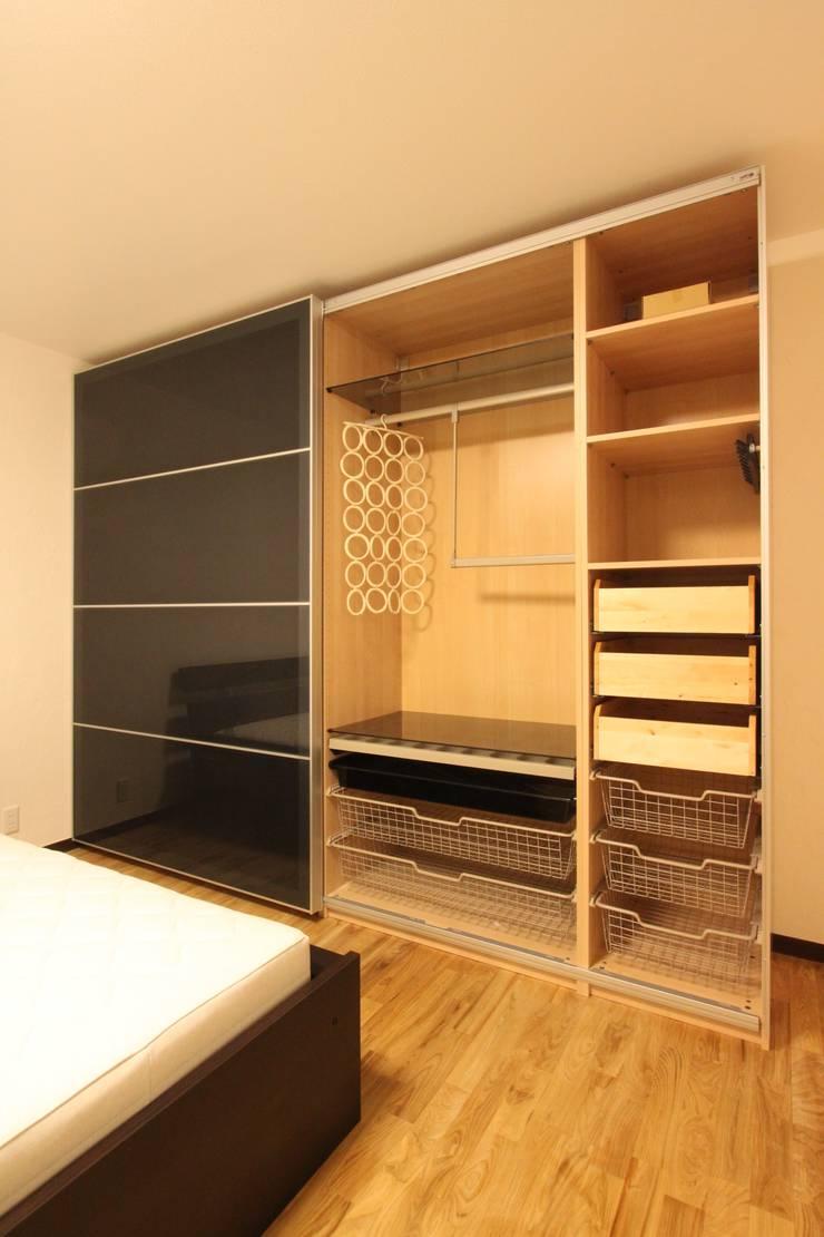 住まいを織る: 有限会社横田満康建築研究所が手掛けた寝室です。