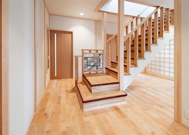 Vestíbulos, pasillos y escaleras de estilo  por マルグラスデザインスタジオ