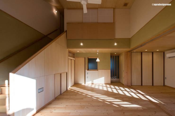 リビングダイニングに続くように介護を考えた寝室を配置する(Al lado de la sala de estar, hay un dormitorio para el cuidado del anciano.): アグラ設計室一級建築士事務所 agra design roomが手掛けたリビングです。,