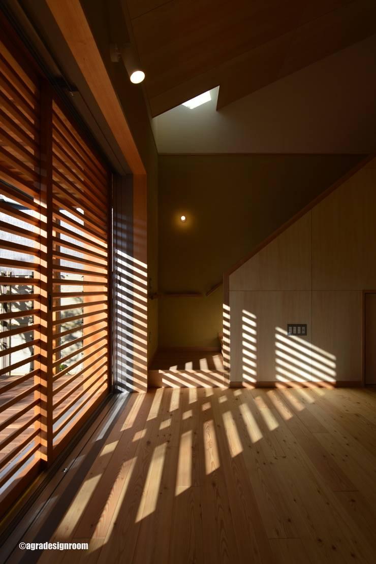 格子の影は、部屋にいろいろな表情を見せる(La rejilla crea varias expresiones en el cuarto.): アグラ設計室一級建築士事務所 agra design roomが手掛けたリビングです。,