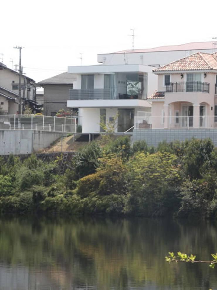 家の裏にある池越し: atelier mが手掛けた家です。,