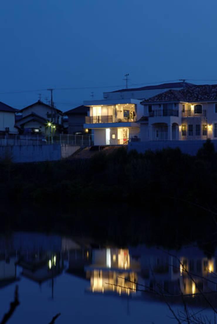 池越しの夕景: atelier mが手掛けた家です。,