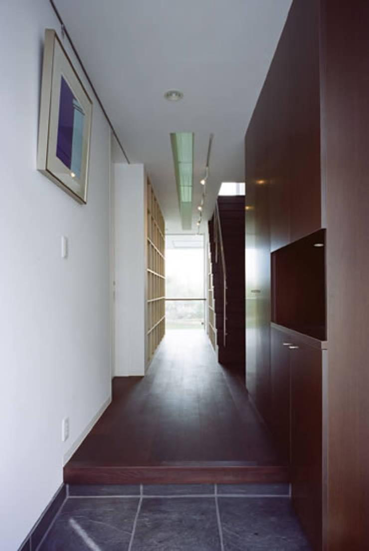 廊下の先にある本棚と書斎: atelier mが手掛けた廊下 & 玄関です。,