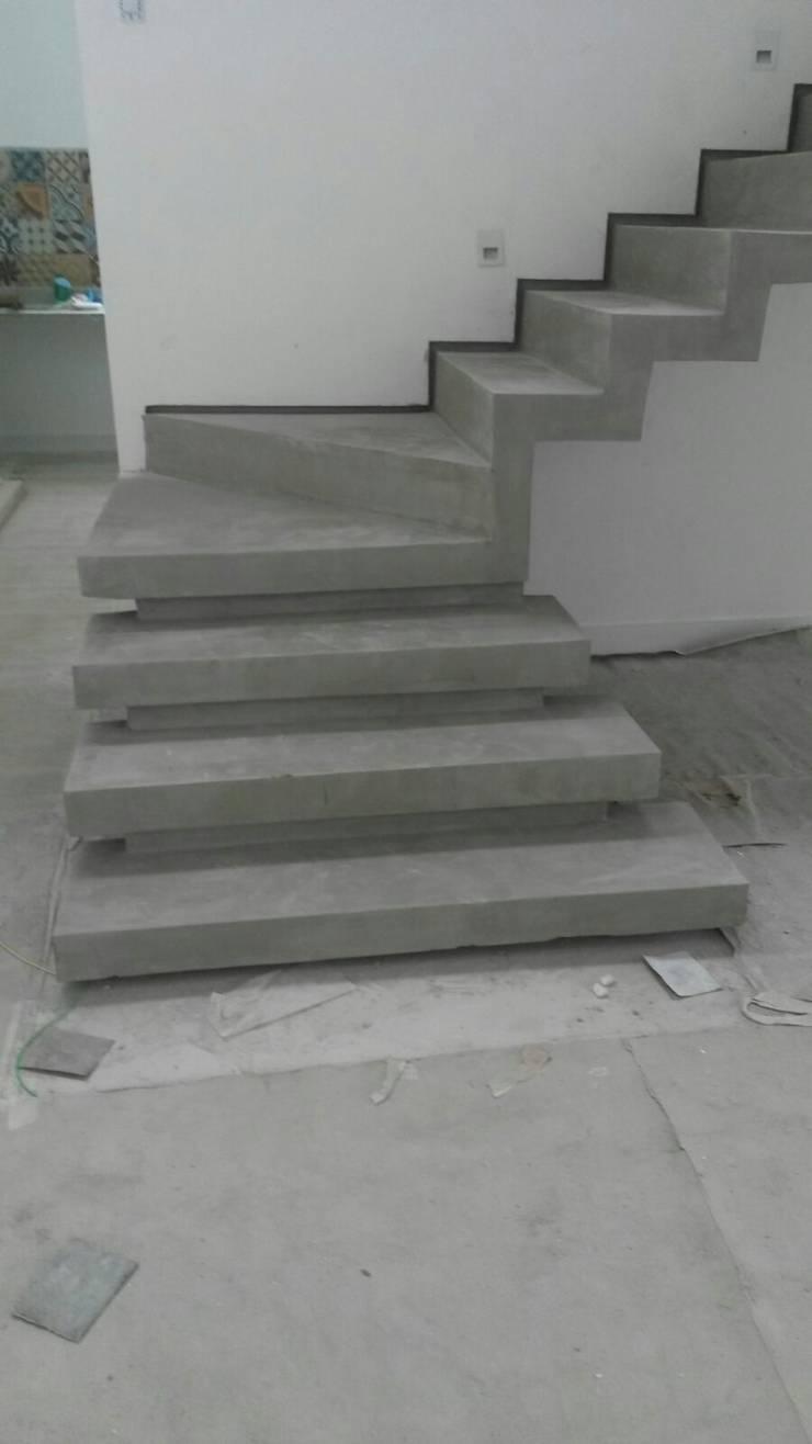 escada em cimento queimado com rodapé invertido: Corredores e halls de entrada  por Margareth Salles