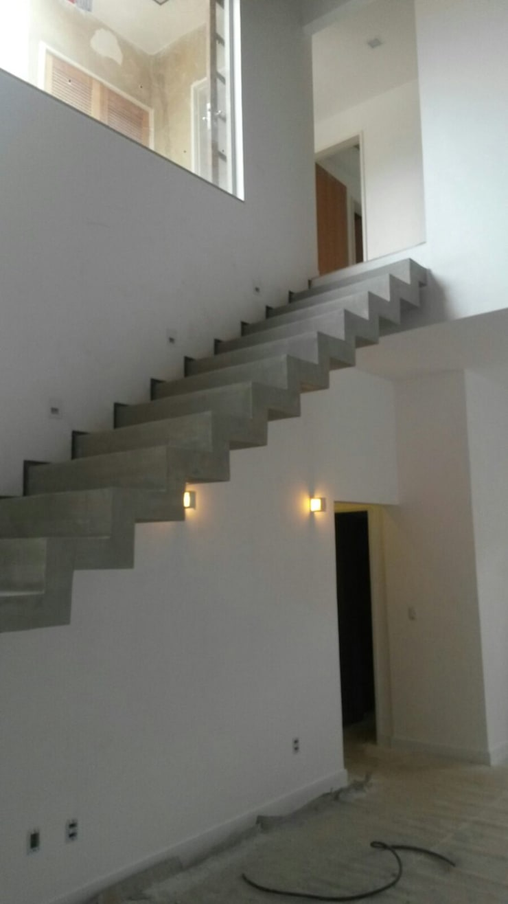escada em cimento queimado e rodapé invertido: Corredores e halls de entrada  por Margareth Salles