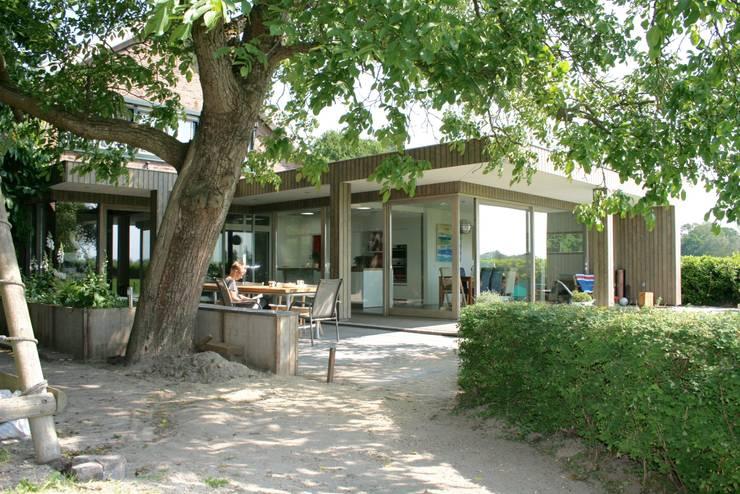 zicht op de beschutte zitplek met tuintafel:   door ddp-architectuur