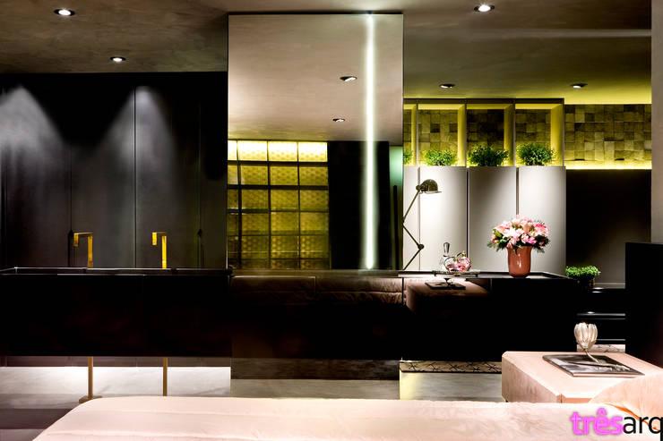 Lavatório integrado ao quarto.: Espaços comerciais  por três arquitetura