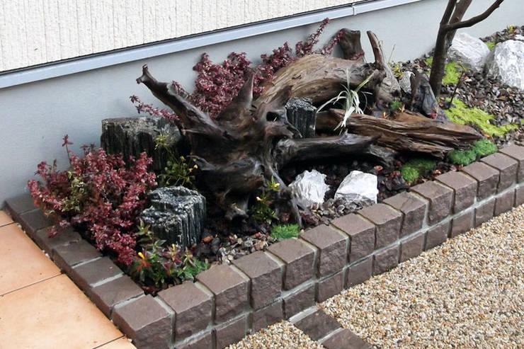 門柱から玄関までのアプローチの花壇をインパクトのある坪庭に: 匠ガーデンが手掛けた庭です。