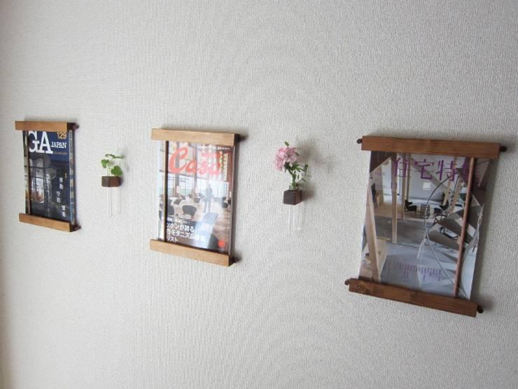 木の壁掛けマガジンラック&一輪挿し: 作房和樂(サボウワラク)が手掛けたリビングルームです。