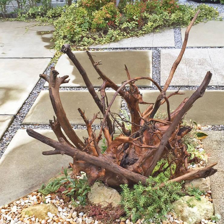 ダイナミックに流木を使った目を引くオブジェ的な植栽: 匠ガーデンが手掛けた庭です。