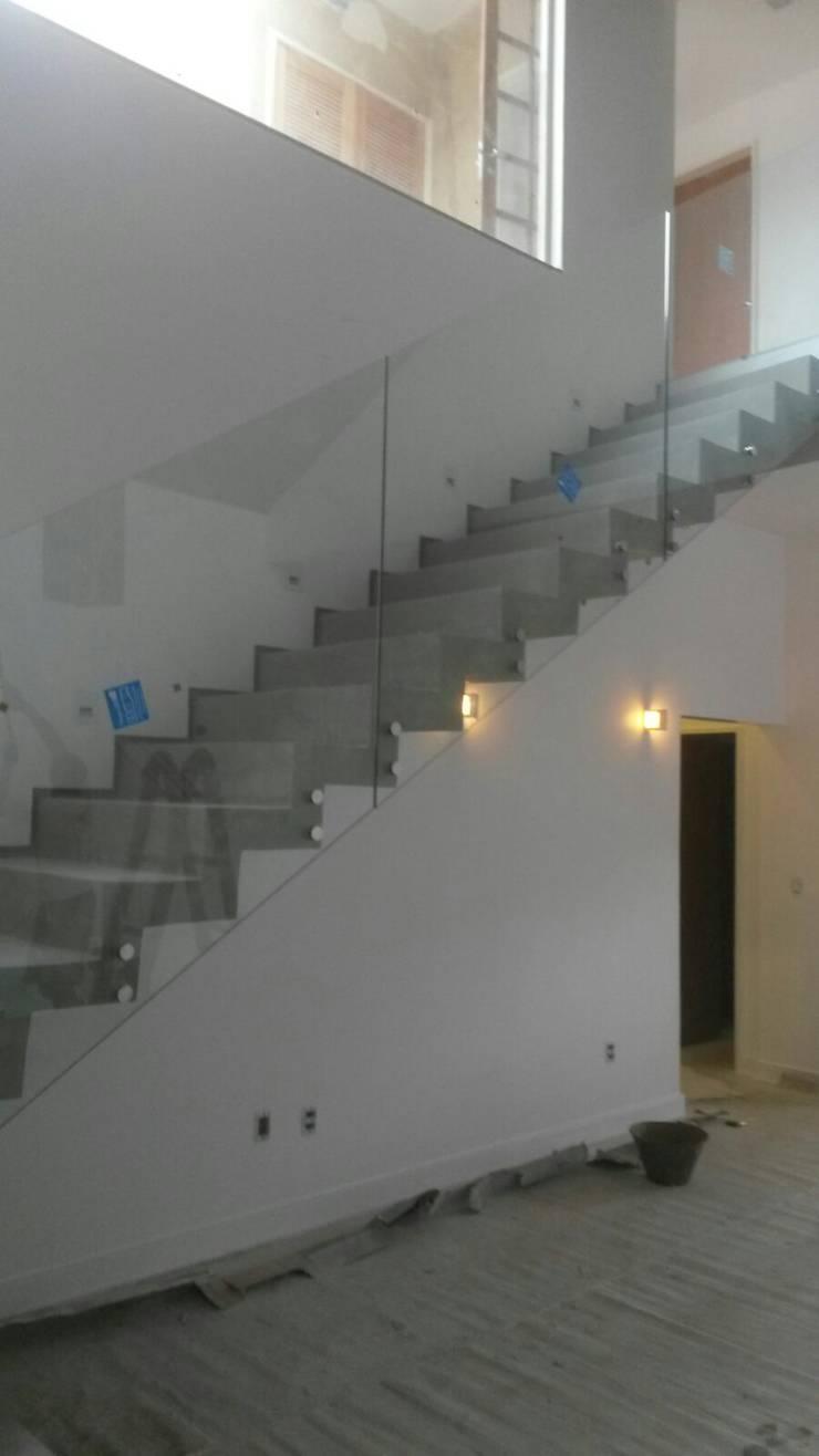 escada em concreto com acabamento em cimento queimado: Corredores e halls de entrada  por Margareth Salles