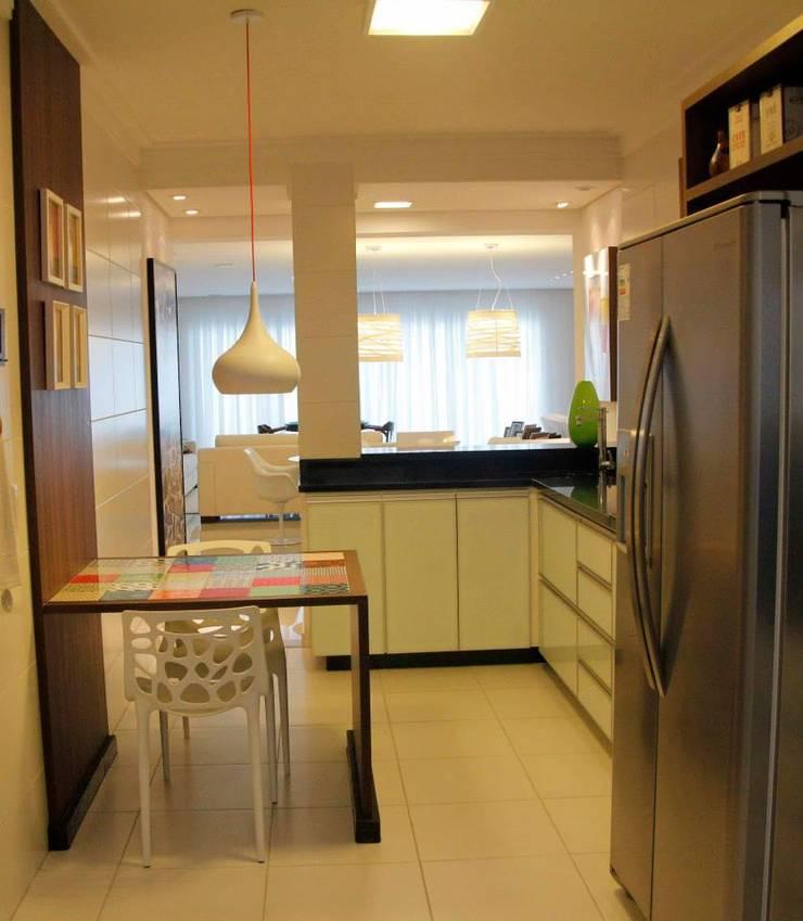 Apt Praia: Cozinha  por Carol Abumrad Arquitetura e Interiores