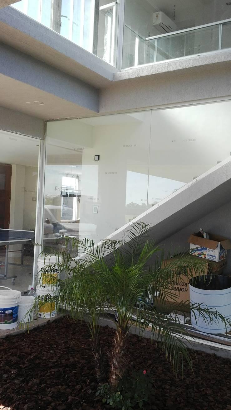 Escalera vidriada - Detalles: Jardines de invierno de estilo  por VHA Arquitectura