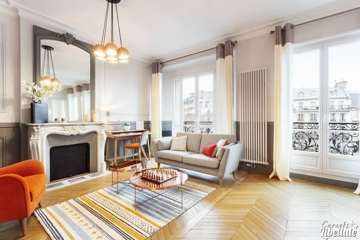 Grand salon avec parquet: Salon de style  par Carnets Libellule