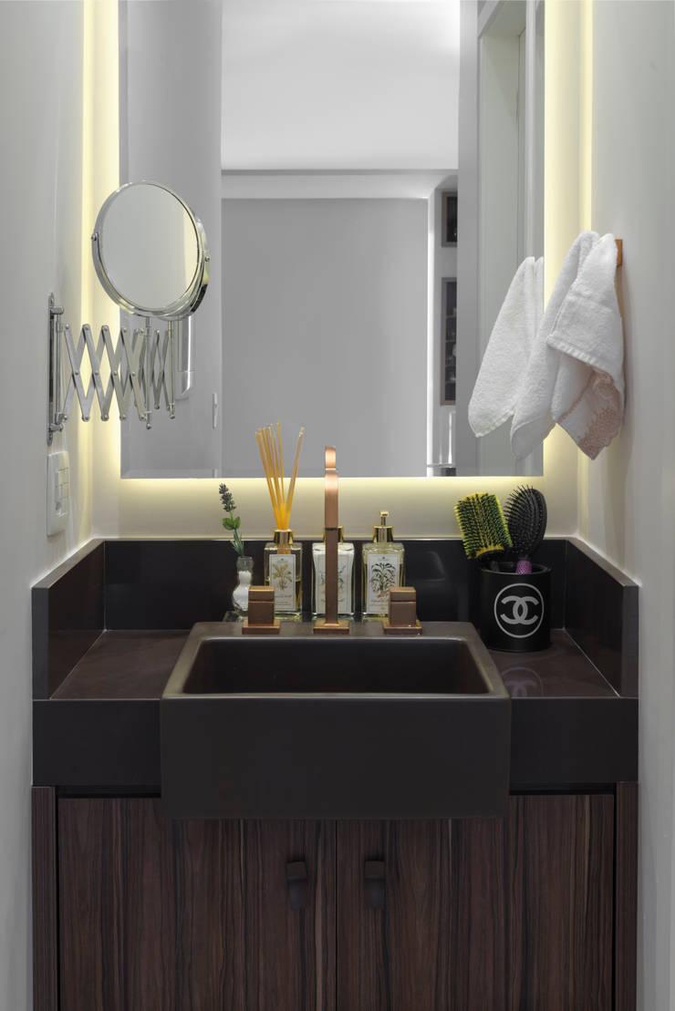 Banheiro com lavatório e espelho com iluminação: Banheiros  por Carina Dal Fabbro Arquitetura e Interiores Ltda