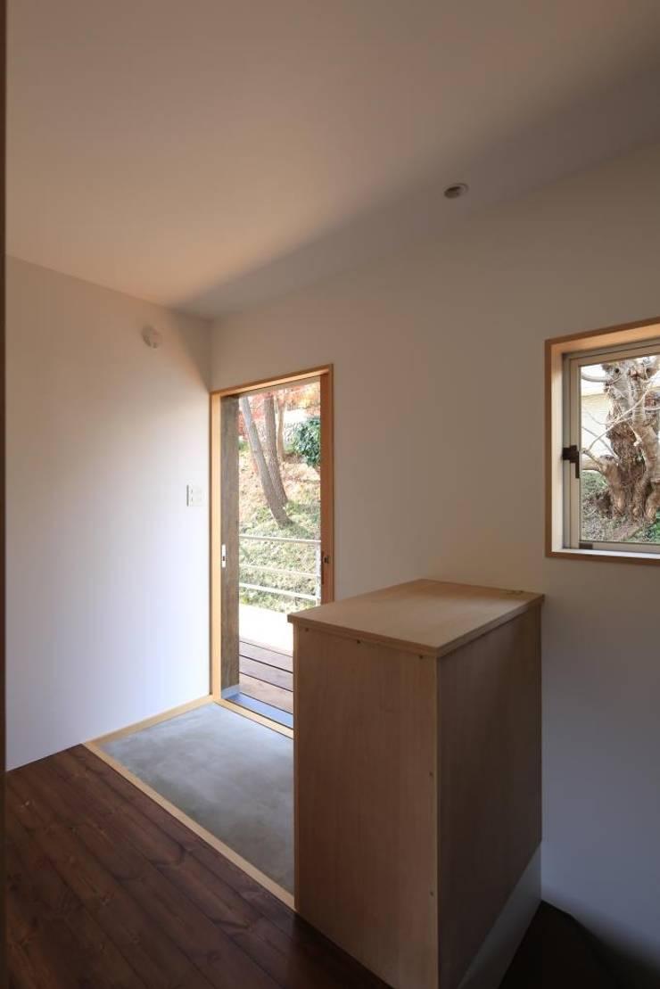玄関(親世帯): 早田雄次郎建築設計事務所/Yujiro Hayata Architect & Associatesが手掛けた廊下 & 玄関です。,