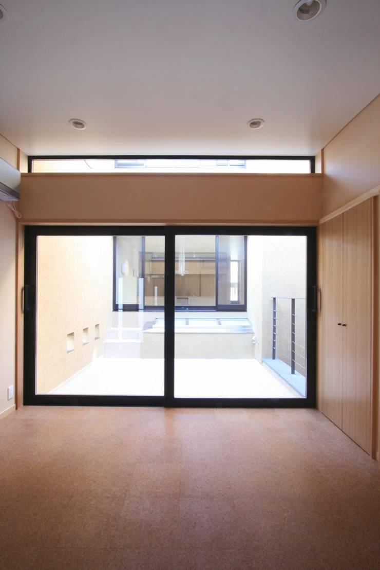 子供室より中庭(光庭)ごしにダイニング・キッチンを望む: 中川龍吾建築設計事務所が手掛けた子供部屋です。