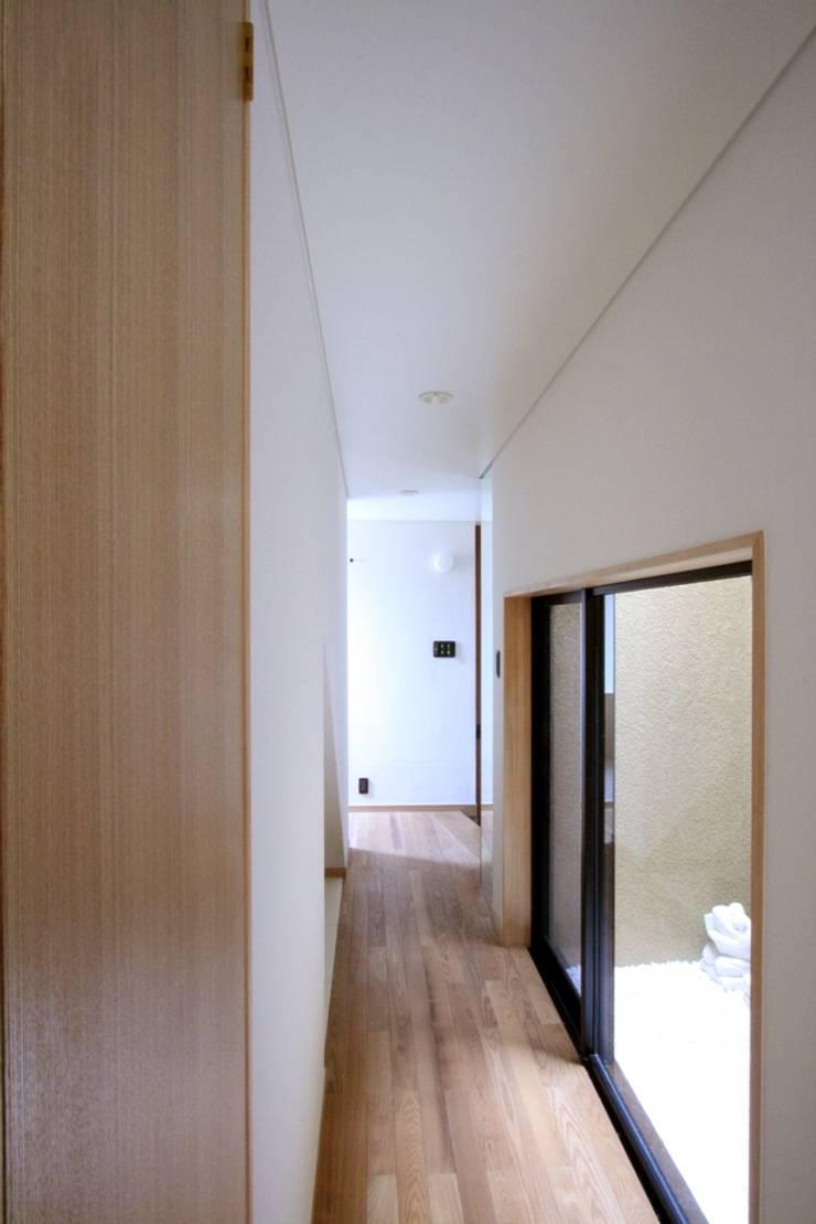 1階の廊下と光庭: 中川龍吾建築設計事務所が手掛けた廊下 & 玄関です。